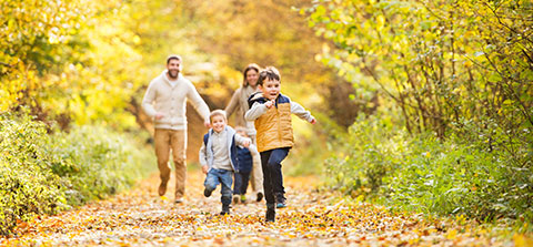 Familie läuft durch einen herbstlichen Wald