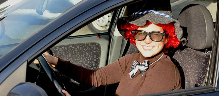 Verkleidete Frau sitzt im Auto